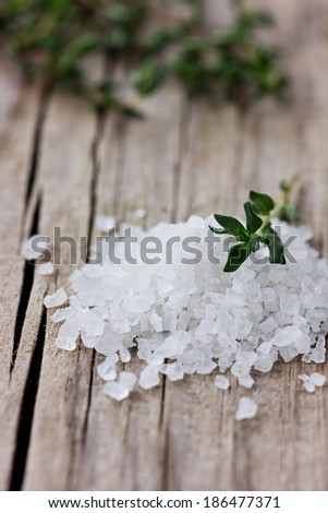 Sea salt with a fresh herbs thyme on a wooden rustic board - stock photo