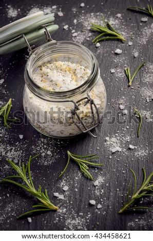 Sea salt with rosemary and lemon zest on black slate board, selective focus - stock photo