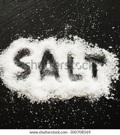 """Sea salt with the inscription """"salt"""" on a dark background, selective focus - stock photo"""