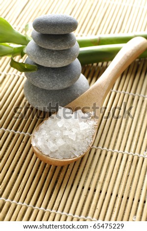 sea salts in wooden bowl with pebble and green bamboo on mat