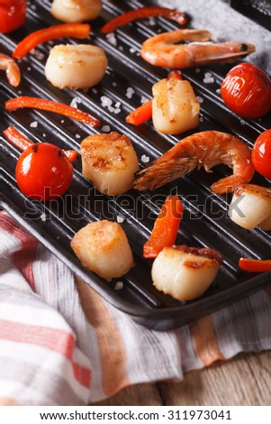 Sea scallops and shrimp are fried on a grill pan close-up. vertical - stock photo