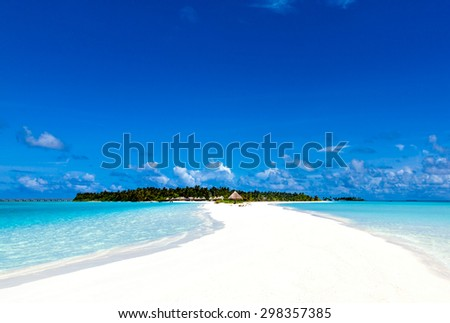 sea shallows leading to tropical island paradise with bungalows and palm trees on the Caribbean Maldivian Hawaii - stock photo