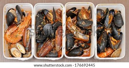 Sea shells and crustacean cooked and served in white plastic containers