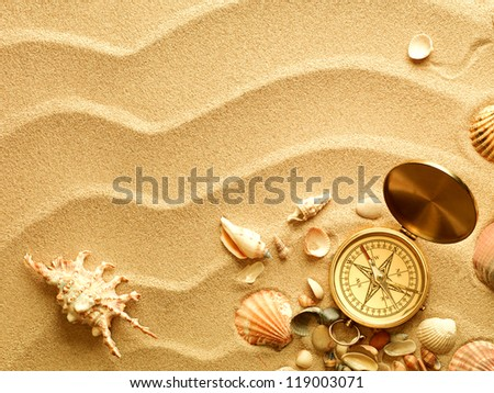 sea shells and old compass with sand as background