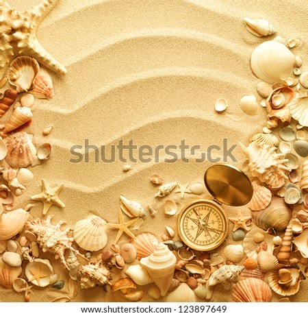 sea shells and old compass with sand as background - stock photo