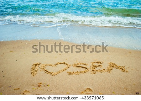 Sea shore and beach with yellow sand with sign I love sea - stock photo