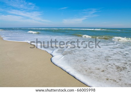 Sea Shore: Gentle waves reach the sand at Assateague Island National Seashore. - stock photo