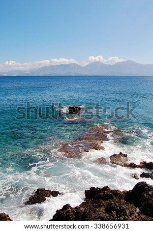 Sea shore on Crete island with mountains on the background