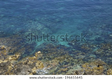 Sea shore with rocks and the blue water