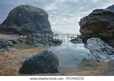 Sea stacks and boulders reflection in sea water on the beach at Bedruthan Steps in early spring with an incoming storm on the North Cornish coast, Cornwall, England, UK - stock photo