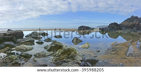 Sea stacks, boulders and rocks, reflections in trapped sea water on the beach at Bedruthan Steps in early spring with an incoming tide on the North Cornish coast, Cornwall, England, UK - stock photo