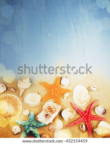 Sea stars and shells on wooden background.