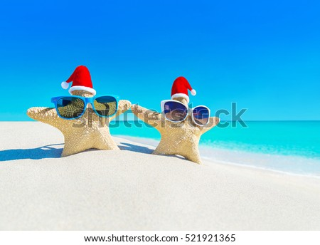 Sea stars couple (starfishes) in sunglasses and red Santa hats at turquoise ocean sandy beach. Merry Christmas and Happy New Year's Day travel destinations concept.