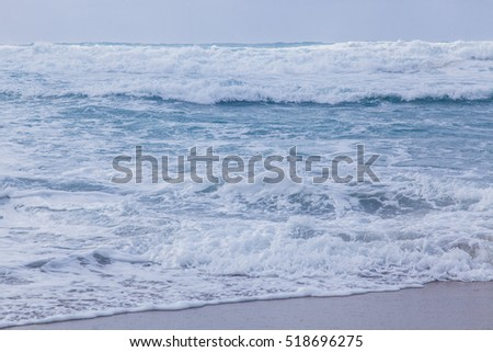 Sea storm in Sardinia. White waves in the blue water.
