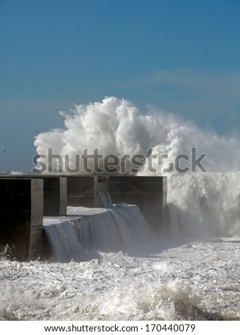 Sea storm with waves crashing against the pier at the mouth of the Douro River on a stormy but clear day - stock photo