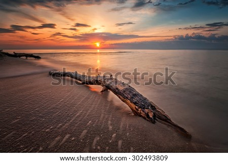 Sea sunrise - Magnificent sunrise view with a stormy sea beach with a log and waves flowing out - stock photo