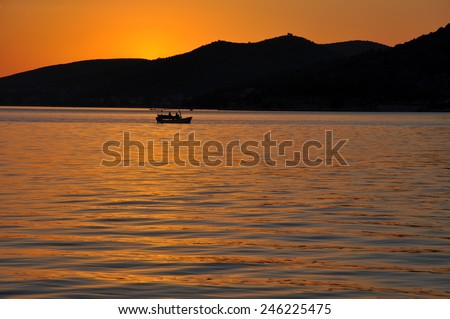 Sea sunset with boat silhouette - stock photo