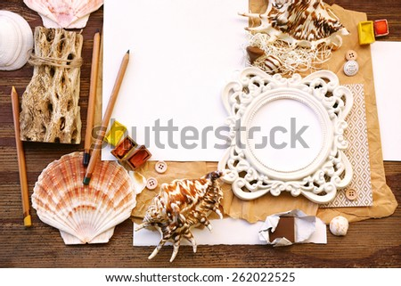 Sea theme composition with shells, pencils unwrapped chocolates and watercolors next to white placeholder paper in the center and artistic rounded photo frame on top of weathered brown vintage wood - stock photo