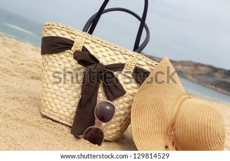 Sea time - seacoast, straw beach bag and sunglasses - stock photo