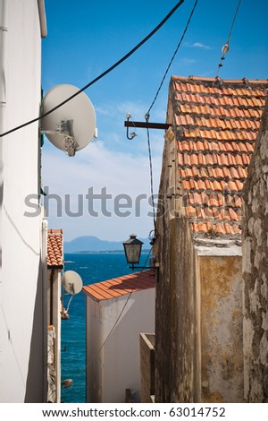 sea view between narrow mediterranean village street - stock photo