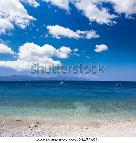 Sea view from pebbles beach with mountains in the background - stock photo
