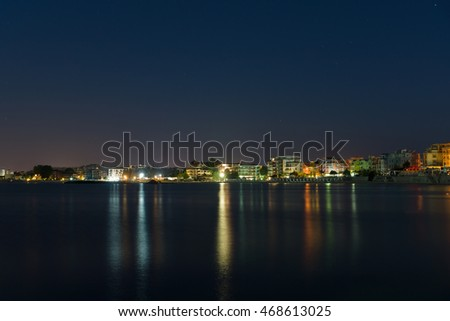 Sea view from the city at night with colored lights