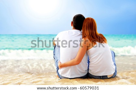 Sea view of a couple sitting on beach.