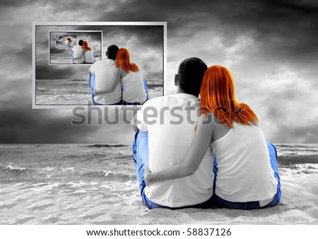 Sea view of a couple sitting on beach and see TV monitor