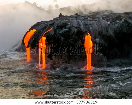 Sea view of Kilauea Volcano in Big Island, Hawaii, United States. A restless volcano that has been in business since 1983. Shot taken at sunset when the lava glows in the dark as jumps into the sea. - stock photo