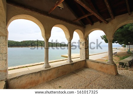 Sea view through arches of small chapel at seaside - stock photo