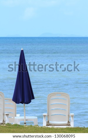 Sea view with blue umbrella and white chairs in Thailand - stock photo