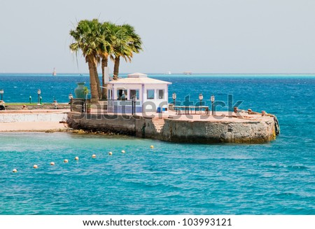 sea view with palms and boat station - stock photo