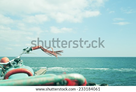Sea, vintage motorcycle and clouds - stock photo