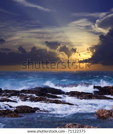 Sea wave breaking against coast  rock in sunset time - stock photo