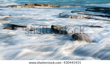 Sea waves crashing on plates of sea rocks creating small waterfalls and smooth streams of water. - stock photo