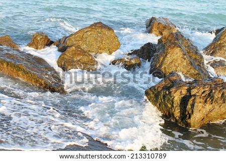 Sea waves hitting the shore rocks - stock photo