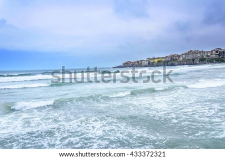 Sea waves on a background of the built-up of shoreline. - stock photo