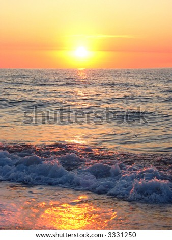 sea waves on a summer sunset with the sun in the center