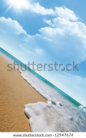 Sea waves on tropical beach and clouds with sun rays in the background - stock photo