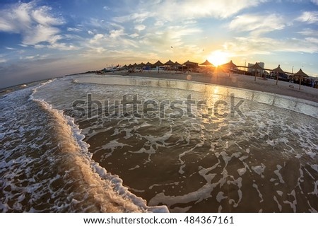 Sea waves rolled on the sandy shore. Beautiful sunset. Sun reflected in water.