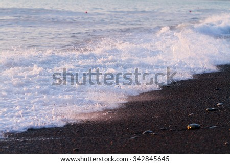 Sea waves with foam and black pebble.