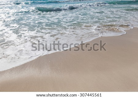 Sea waves with foam on white tropical sandy beach