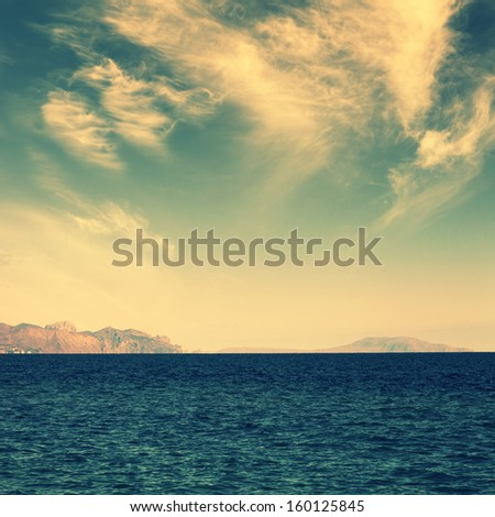 sea with island on horizon and clouds on sky, vintage colors - stock photo