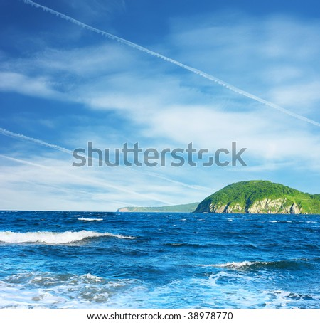 Sea with waves and green island
