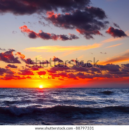 Sea with waves and sunset with cloudy sky - stock photo
