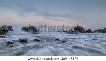 Sea with waves crashing on the rocks, gentle transitions, blur, splash, sunset (sunrise), quiet atmosphere, intimate. The coastline of the surf. Art photo.