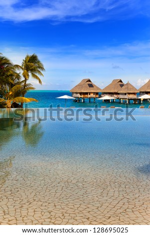 seacoast with palm trees and small houses on water. - stock photo