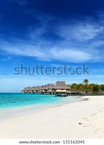 seacoast with palm trees and small houses on water - stock photo