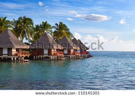 Seacoast with palm trees and small houses on water on a sunset - stock photo