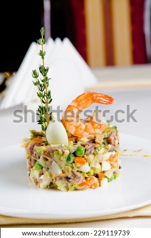 Seafood appetizer with pink prawn, herbs, hard-boiled egg and diced vegetables in a savory mousse served at a table in a restaurant - stock photo
